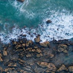 morski valovi butajo ob skale, pogled iz vrha