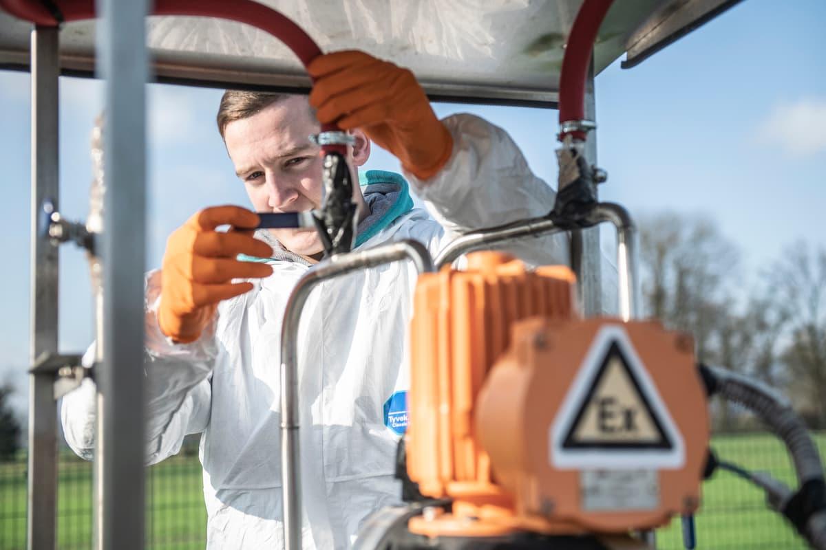 delavec v zaščitni obleki dela na čistilni napravi